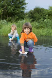 Three boy play in puddle Stock Images
