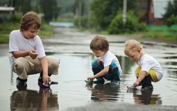 Three boy play in water Stock Image