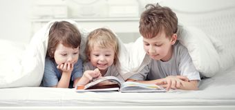 Three boy read book indoors on bed.  royalty free stock photography