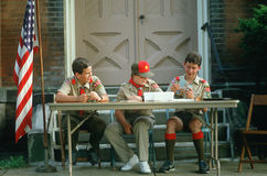 Three Boy Scouts seated at table Royalty Free Stock Photography