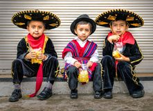 Three boys in caballero costumes sit on a ledge eating potato ch Stock Photography