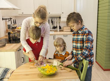 Three boys cutting vegetables with mother Royalty Free Stock Image