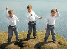 Three boys dance on green grass Stock Image