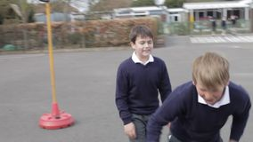 Three Boys Fighting In School Playground. Two boys punching one another in playground fight. Shot on Canon 5d Mk2 with a frame rate of 30fps stock video footage