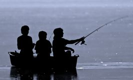 Three boys fishing. From a boat in silhouette royalty free stock image