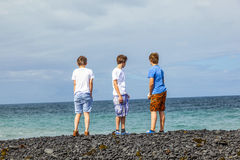 Three boys have fun at the black volcanic beach Stock Photo