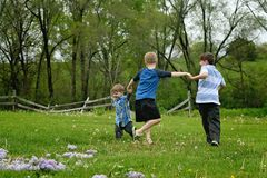 Three boys holding hands running. Three little boys running in a circle, playing and holding hands. Rural setting stock images