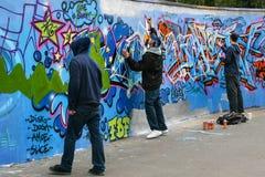 Three boys painting grafitti stock photo