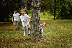 Free Three Boys Peeking Around Trees Stock Images - 123699974