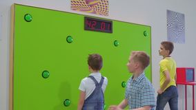 Three boys play a game of reaction speed in scientific museum. The boys play in the game in scientific museum. They pushes buttons on green wall and checks their stock footage