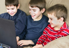 Three Boys Playing. A group of three boys playing on computer together Stock Photo