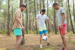 Three boys playing football in forest Stock Image