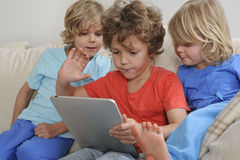 Three boys playing game on tablet Stock Images