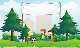 Three boys playing soccer below an empty banner Royalty Free Stock Image