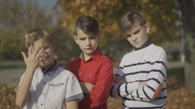 Three boys posing at the camera and straightes hair outdoors. Boys spend time together. stock footage