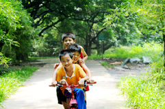 The three boys riding on bicycle Stock Photography