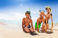 Happy friends sitting on sandy beach in scuba mask Stock Photography