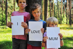Three boys with sign I love mum Royalty Free Stock Images