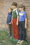 Three boys standing in front of a brick wall in Harrison, ID Royalty Free Stock Photo