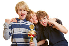 Three boys with trophy cheering Stock Image