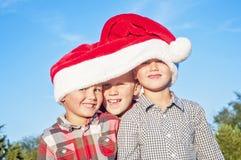 Three boys wearing Santa hat Stock Image