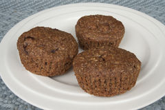 Three bran muffins on white plate Royalty Free Stock Photo