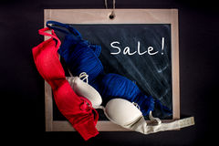 Three brassieres lying on the chalkboard sale. Three brassieres lying on the chalkboard with the word sale Royalty Free Stock Photo