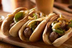 Free Three Bratwurst Sausages With Grilled Onions And Bell Peppers Royalty Free Stock Photo - 143864235