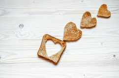Three bread croutons in the form of hearts and a toast with Cutting inside heart lie on a wooden surface. royalty free stock photo