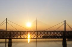Three bridges and train at sunset Royalty Free Stock Photography