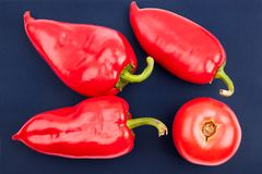 Three bright big red bell peppers and one red tomatoe on blue background top view closeup royalty free stock photo