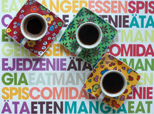 Three bright coffee cups with hot espresso on a colorful surface Stock Image