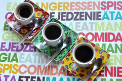Three bright coffee cups with hot espresso on a colorful surface Stock Photography