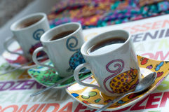 Three bright coffee cups with hot espresso on a colorful surface Royalty Free Stock Images