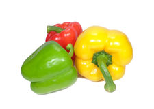 Three bright color ripe bell peppers, one green, one yellow and one red isolated on white background Royalty Free Stock Images