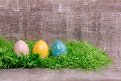 Three colorful eggs on a green grass in front of a wooden background. Easter greeting card. royalty free stock photo