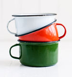 Three bright colorful enameled mugs Royalty Free Stock Photography