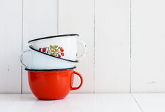 Three bright colorful enameled mugs Stock Images