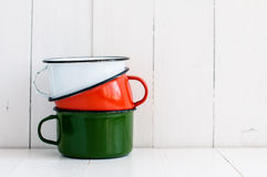 Three bright colorful enameled mugs. A stack of three bright colorful enameled mugs on white painted wooden table, kitchenware and decor, rustic vintage kitchen Stock Photo