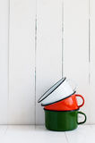 Three bright colorful enameled mugs Stock Photos
