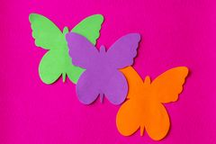 Three bright and coloured butterflies made of soft material on a fuchsia rag background stock photography