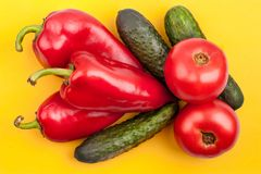 Three bright red peppers, three green cucumbers and two red tomatoes on yellow background top view close up stock photography
