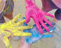 Three brightly colored hands together. royalty free stock photography