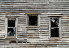 Three Broken Windows in a Dilapidated Wooden House Stock Photos