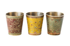 Three bronze cup with ornament on a white background. Three bronze yellow cup with ornament on a white background stock photo