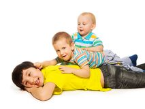 Three brothers. Laying on each other and having fun stock photos