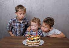 Three brothers blow out candles on birthday cake royalty free stock photos