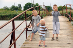 Three brothers came to the bridge in the village across the river to fish but instead ran along the bridge from the excess of feel. Ings with a tourist aluminum royalty free stock photo