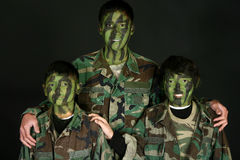 Three Brothers in Camo. Three handsome Filipino brothers in camo paint and fatigues over black royalty free stock image