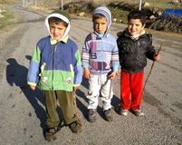 Three brothers. Three children standing on a road in a village of kurdistan, they are playing with sticks royalty free stock images